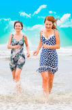 Beautiful people running at ocean Stock Images