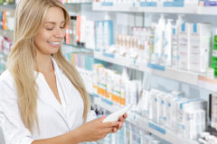 Beautiful pharmacist choosing the product Royalty Free Stock Photography