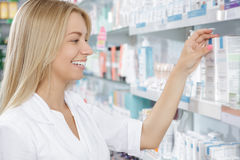 Beautiful pharmacist choosing the product Stock Images