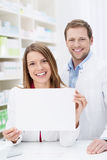 Beautiful pharmacist displaying a blank sign Stock Photography
