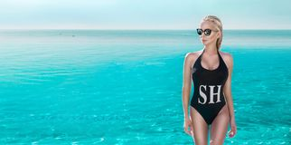 Beautiful phenomenal stunning elegant luxury sexy blonde model woman with perfect face in bikini and sunglasses standing in the po Stock Images