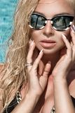 Beautiful phenomenal stunning elegant luxury sexy blonde model woman with perfect face in bikini and sunglasses standing in the po Royalty Free Stock Photography