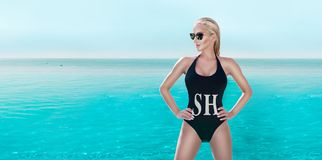 Beautiful phenomenal stunning elegant luxury sexy blonde model woman with perfect face in bikini and sunglasses standing in the po Stock Photos