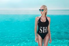 Beautiful phenomenal stunning elegant luxury sexy blonde model woman with perfect face wearing a sunglasses stands with elegant sw. Imsuit on amazing view with Royalty Free Stock Photos