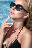 Beautiful phenomenal stunning elegant luxury sexy blonde model woman with perfect face wearing a sunglasses stands with elegant sw Stock Image
