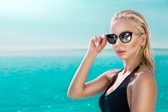 Beautiful phenomenal stunning elegant luxury sexy blonde model woman with perfect face wearing a sunglasses stands with elegant sw. Imsuit on amazing view with Stock Photography