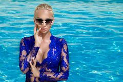 Beautiful phenomenal stunning elegant luxury sexy blonde model woman with perfect face wearing a sunglasses stands with elegant sw. Imsuit on amazing view with Royalty Free Stock Photography