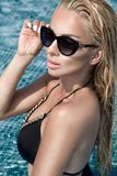 Beautiful phenomenal stunning elegant luxury sexy blonde model woman with perfect face wearing a sunglasses stands with elegant sw Royalty Free Stock Images
