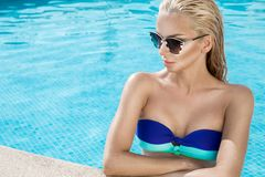 Beautiful phenomenal stunning elegant luxury sexy blonde model woman with perfect face wearing a sunglasses stands with elegant sw Royalty Free Stock Image
