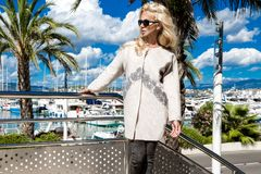 Beautiful phenomenal stunning  elegant luxury sexy blonde model woman wearing a coat and boots and sunglasses stands on a yacht. In Cannes, France Royalty Free Stock Image