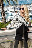 Beautiful phenomenal stunning elegant luxury sexy blonde model woman wearing a coat and boots and sunglasses. Stands on a yacht in Cannes, France Stock Photo