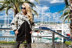 Beautiful phenomenal stunning  elegant luxury sexy blonde model woman wearing a coat and boots and sunglasses. Stands on a yacht in Cannes, France Stock Image