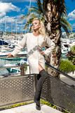 Beautiful phenomenal stunning  elegant luxury sexy blonde model woman wearing a coat and boots and sunglasses. Stands on a yacht in Cannes, France Royalty Free Stock Photo