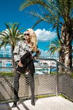 Beautiful phenomenal stunning  elegant luxury sexy blonde model woman wearing a coat and boots and sunglasses. Stands on a yacht in Cannes, France Stock Photos