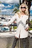 Beautiful phenomenal stunning  elegant luxury sexy blonde model woman wearing a coat and boots and sunglasses stands on a yacht. In Cannes, France Royalty Free Stock Images