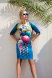 Beautiful phenomenal stunning elegant luxury sexy blonde model woman wearing a dress and high heels and sunglasses stands on amazi Stock Photos