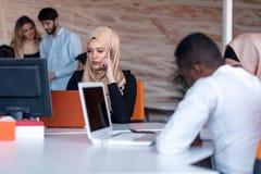 Beautiful phone operator Arab woman working in modern startup office. Beautiful phone operator Arab women working in modern startup office Royalty Free Stock Photos