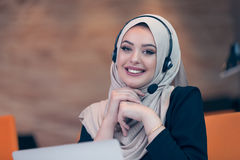 Beautiful phone operator arab woman working in startup office. Beautiful phone operator arab woman working isolated on a white background Stock Photos