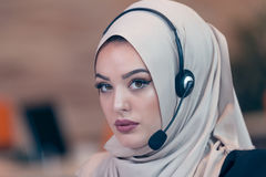 Beautiful phone operator arab woman working in startup office. Beautiful phone operator arab woman working isolated on a white background Royalty Free Stock Image