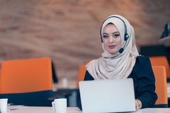 Beautiful phone operator arab woman working in startup office. Beautiful phone operator arab woman working  on a white background Stock Photography
