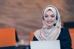 Beautiful phone operator arab woman working in startup office. Beautiful phone operator arab woman working  on a white background Royalty Free Stock Image