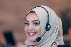 Beautiful phone operator arab woman working in startup office. Beautiful phone operator arab woman working  on a white background Royalty Free Stock Photos