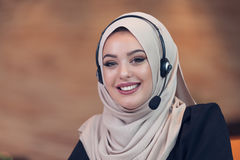 Beautiful phone operator arab woman working in startup office. Beautiful phone operator arab woman working  on a white background Stock Image