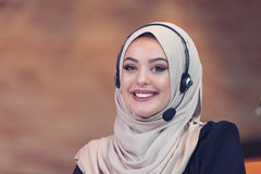 Beautiful phone operator arab woman working in startup office royalty free stock photography