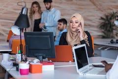 Beautiful phone operator Arab woman working in modern startup office. Beautiful phone operator Arab women working in modern startup office Royalty Free Stock Photography