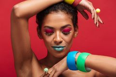 Beautiful photo of half-naked mulatto woman with trendy makeup d. Emonstrating colorful bracelets on camera over red background Stock Photo