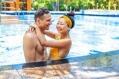 Beautiful photo of happy couple in the pool chatting with each other. royalty free stock photos