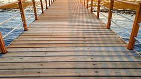 Beautiful image of long wooden pier in the ea. Amazing sunset over the bridge in ocean royalty free stock image