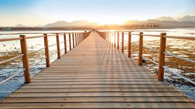 Beautiful image of long wooden pier in the ea. Amazing sunset over the bridge in ocean stock image