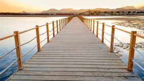 Beautiful image of long wooden pier in the ea. Amazing sunset over the bridge in ocean royalty free stock images