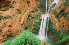 Beautiful photo of Ouzoud waterfall in Morocco with soft flowing water and large colored rocks. Green wild jungles on Royalty Free Stock Image