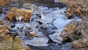 Water flowing down a rocky, icy creek. stock video