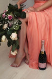 Beautiful photo of woman's legs, bottle of champagne and flowers Royalty Free Stock Photos