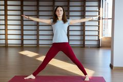 Beautiful photo of young lady standing in bridge exercise while practicing yoga poses on yoga mat royalty free stock photo
