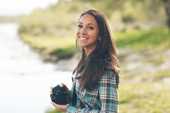 Beautiful photographer portrait. Beautiful smiling female photographer posing and holding a digital camera, natural landscape on background Stock Photos