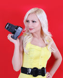 Beautiful photographer with the professional camera over red Royalty Free Stock Photos