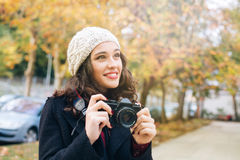 Beautiful photographer woman in autumn. Happy young beautiful woman with an analog camera capturing autumn in the city Royalty Free Stock Photography