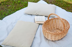 Beautiful picnic with tablecloth , pillows , book and food baske Stock Image