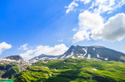 Beautiful picture of the alpine landscape with snow and green me Stock Photos