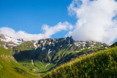Beautiful picture of a green mountaintops with a little snow Royalty Free Stock Photography