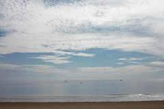 Beautiful picture of sand beach and blue sea under the cloudy sky Royalty Free Stock Images