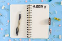 Picture from the top. Notepad on springs with an inscription Goals . Chaotically scattered office supplies on a blue. Beautiful picture from the top. Notepad on Royalty Free Stock Images