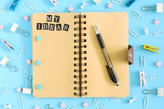 Picture from the top. Notepad on springs with an inscription My Ideas. Chaotically scattered office supplies on a blue. Beautiful picture from the top. Notepad Stock Photos