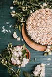 Beautiful pie with white meringue cream on a wooden background among white flowers. Viewpoint from above. Beautiful pie with white meringue cream on a wooden