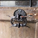 Beautiful old cast-iron door handle on an old peeling door in Prague. royalty free stock image