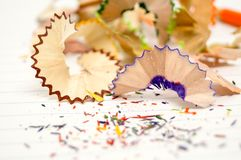 Beautiful piece of wood junk from sharpener crayon. Beautiful piece of wood junk from sharpener crayon on a paper and many colorful pieces Royalty Free Stock Image